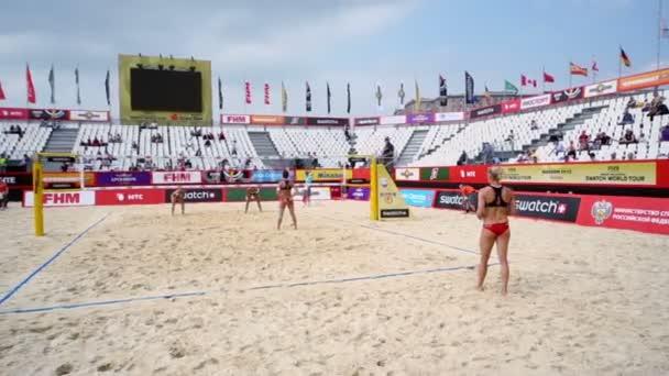 Woman serves in beach volleyball match