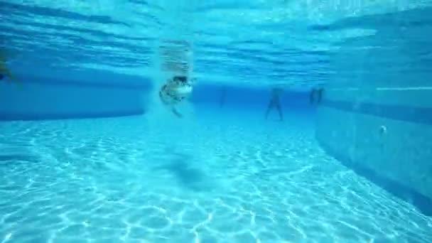 Podvodní pohled na ženu, plavání v bazénu
