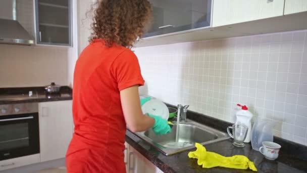 Niedliche Hausfrau spült Geschirr