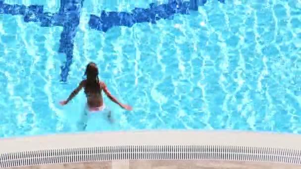 Malá holčička skáče v modré vodě