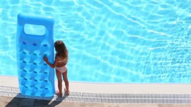 Malá holčička stojí s nafukovací matrace