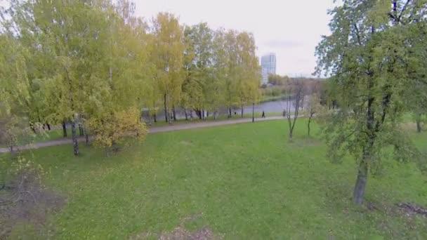 People walk by path among trees near Cherkizovsky pond