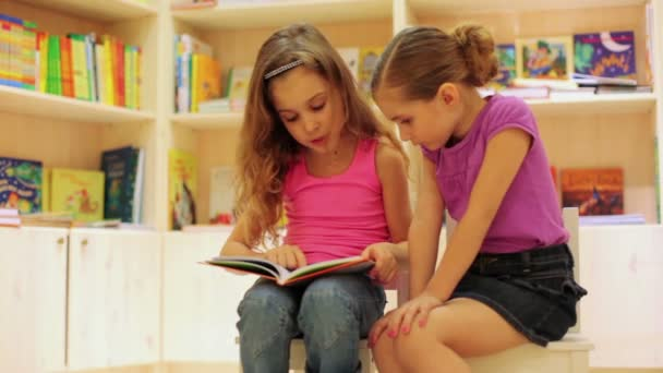 Two little girls reading book
