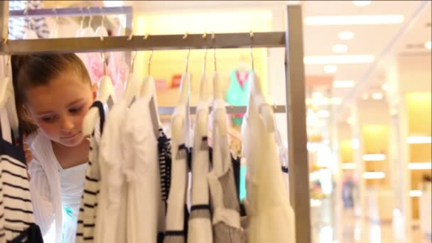 Little girl looks over hangers with clothing