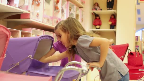 Dvě dívky, které jsou umístěny panenku v kočárku