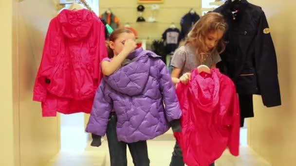 Dvě dívky zavěšení bundy na ramínka