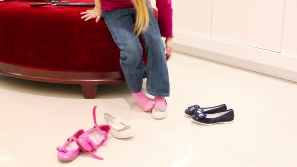 Mädchen im Schuhgeschäft wählt Schuhe