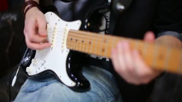 Young man plays electric guitar
