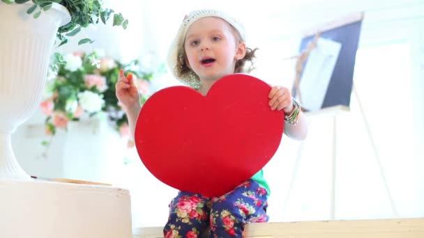 little girl with board in shape of heart