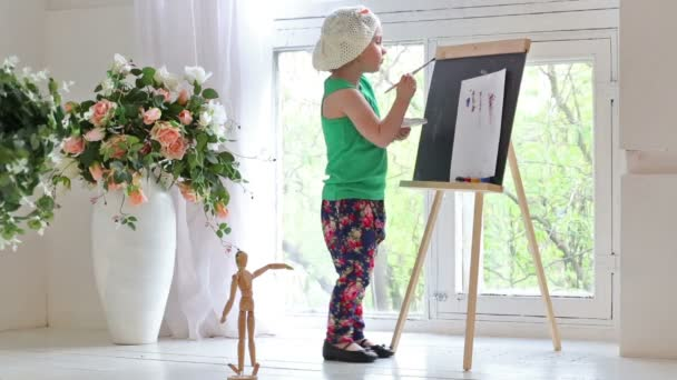 Little girl drawing on easel