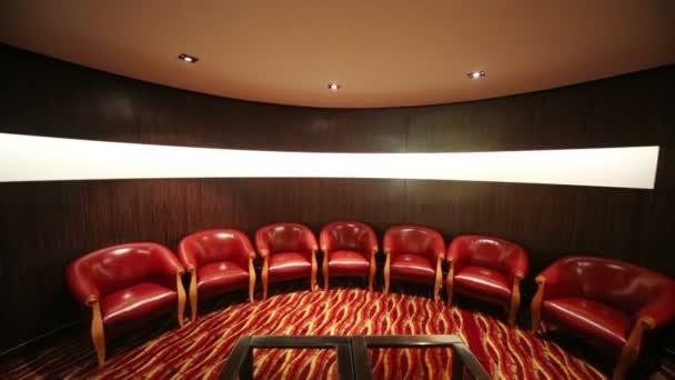 malý pokoj s červenými koženými křesly