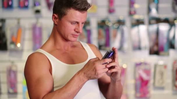 svalnatý muž při pohledu na mobilní telefon