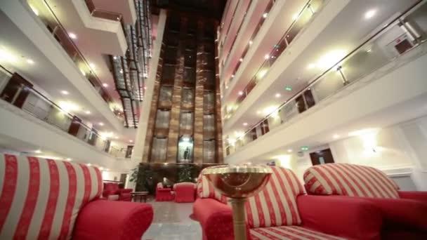 Atrium s červenými křesly v hotelu