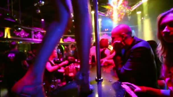 Go-go girl dances at pole on bar