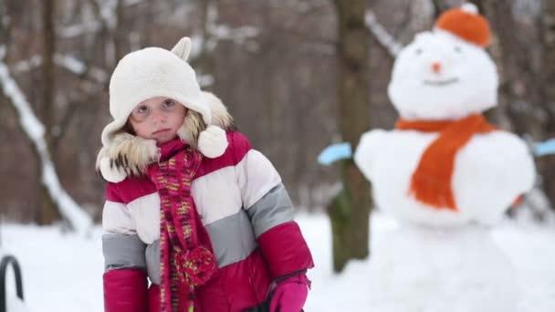 Kislány mellett álló hóember