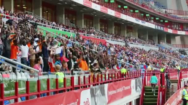 Fans raise their arms on match at Stadium