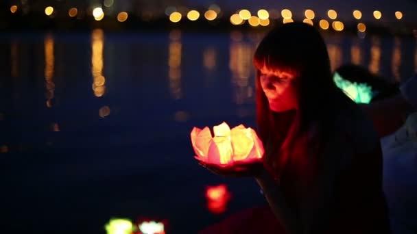 Beautiful woman looks at water lantern
