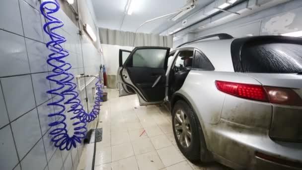 Špinavé a mokré šedé auto v dílně