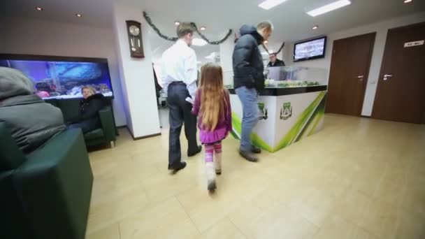 Man walks with daughter in hall