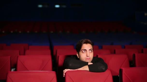 Junger Mann sitzt im Kinosaal