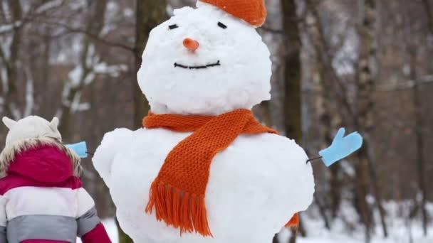 kleines Mädchen in der Nähe eines Schneemanns im Winterpark