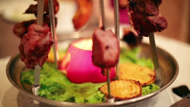 Grilled meat on skewers on spinning plate