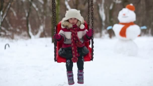 Little girl on swing at winter park