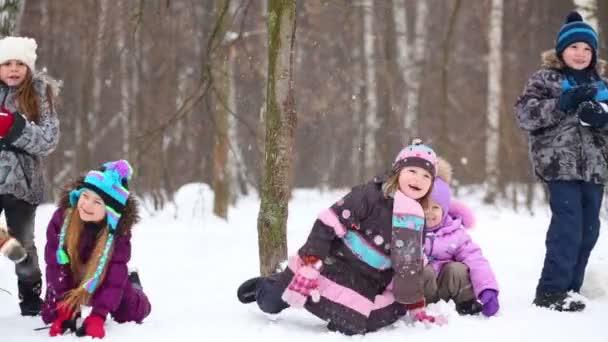 Fünf Kinder werfen Schneebälle
