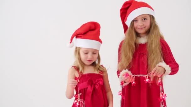 Two girls in caps Santa Claus