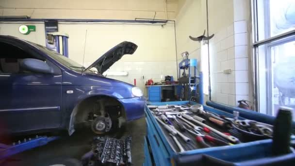 Blue car with open hood in workshop