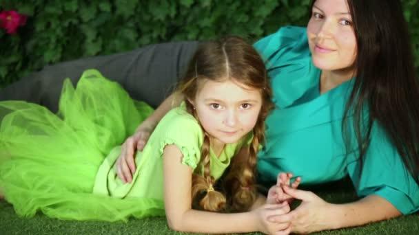 Mutter und Tochter liegen auf Rasen