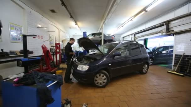 Worker, cars and lift in workshop