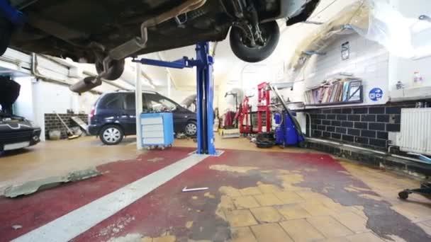 Under car on lift in workshop