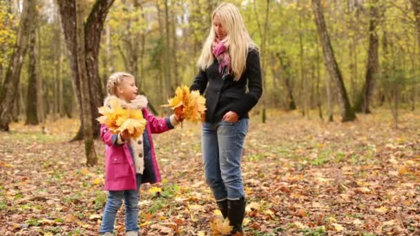 Little daughter and mother hold leaves