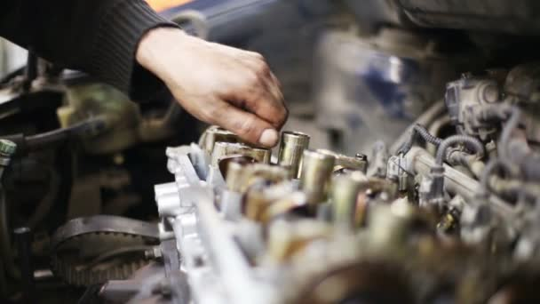 mechanic unscrews bolt of car engine