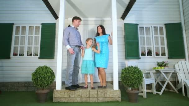 Otec, matka a dcera stojí na verandě