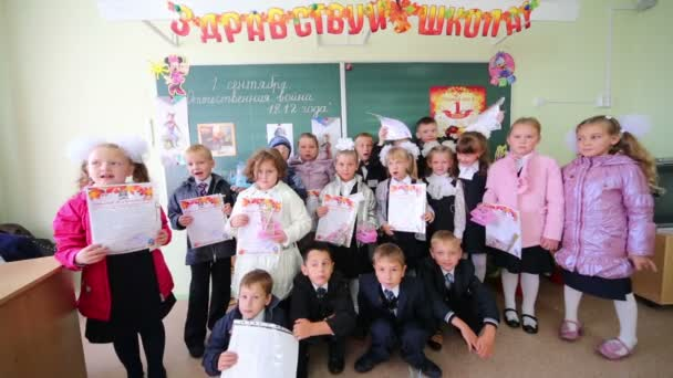 Dressed first-graders with gifts in hands