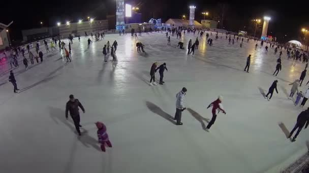 People slide on skates by ice of rink