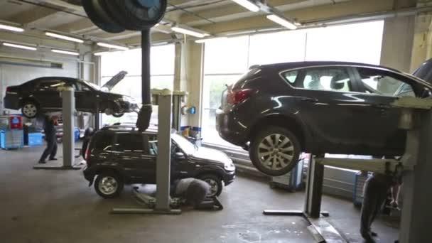 Pracovníci opravují automobily ve výtazích v dílně