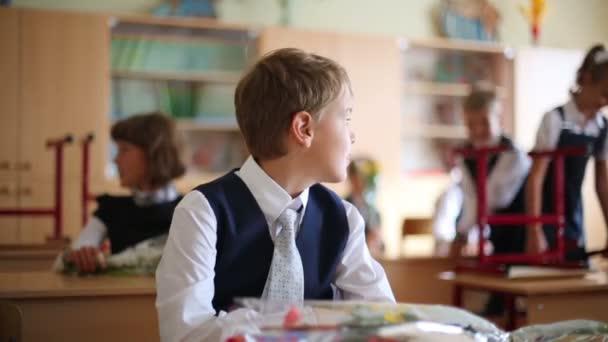 Schoolboy ül az íróasztalán az osztályban