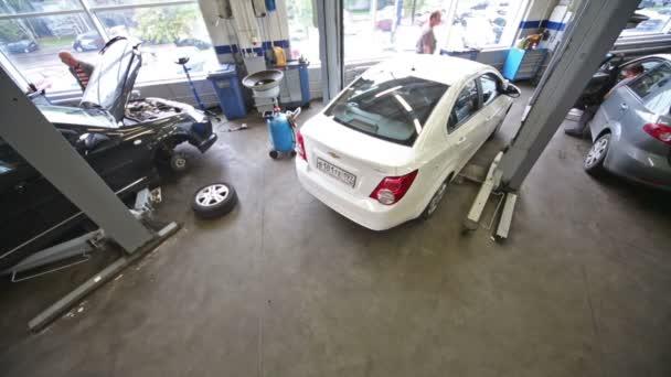 White car leaves lift at workshop