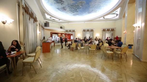 Lidé jedí v kavárně v akademickém divadle