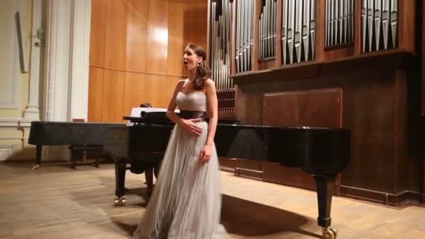 žena pianista hrající klavír a zpěvák
