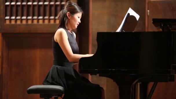 Půvabná žena pianista sedí na klavír