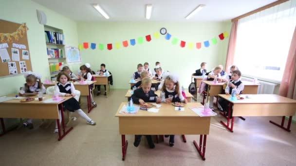 Első osztályú tanulók ülnek íróasztalok