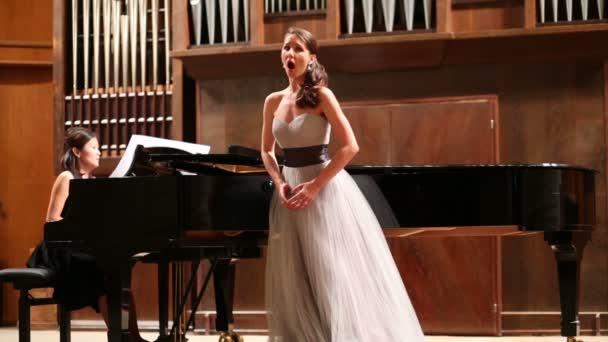 Nő zongorista és énekes énekel
