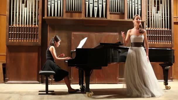 Játszik a zongorista és énekes énekel opera