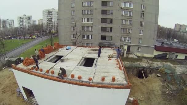 Arbeiter bauen Ziegelmauer