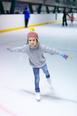 Adorable little girl wearing jeans, warm sweater and colorful hat skating on ice rink stock vector