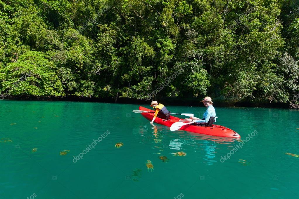 Family kayaking in ocean among jellyfish